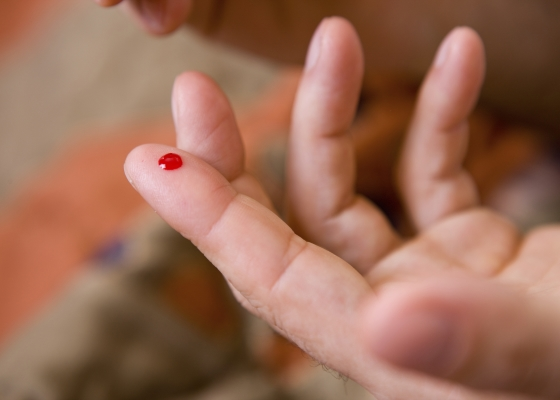 Hand with blood drop for Point of Care testing